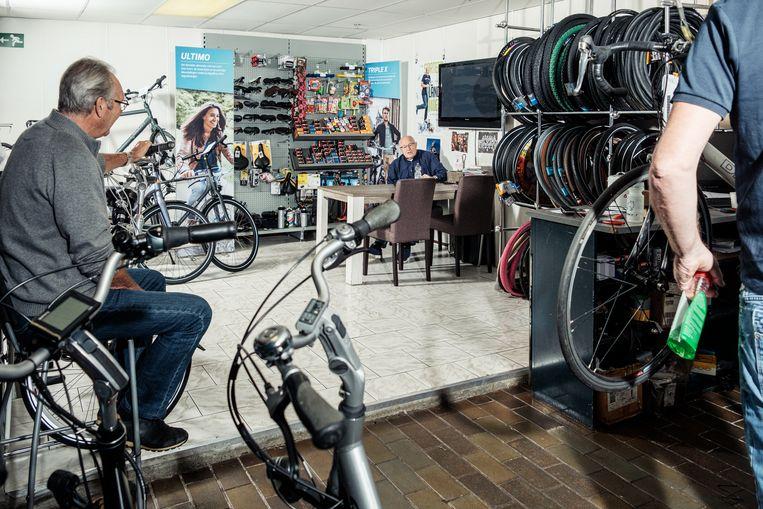 """Rinus Israël aan zijn vaste tafel bij fietsenzaak Dral in Landsmeer. """"Jullie zijn hier maar wat blij met me."""" Beeld Jakob Van Vliet"""