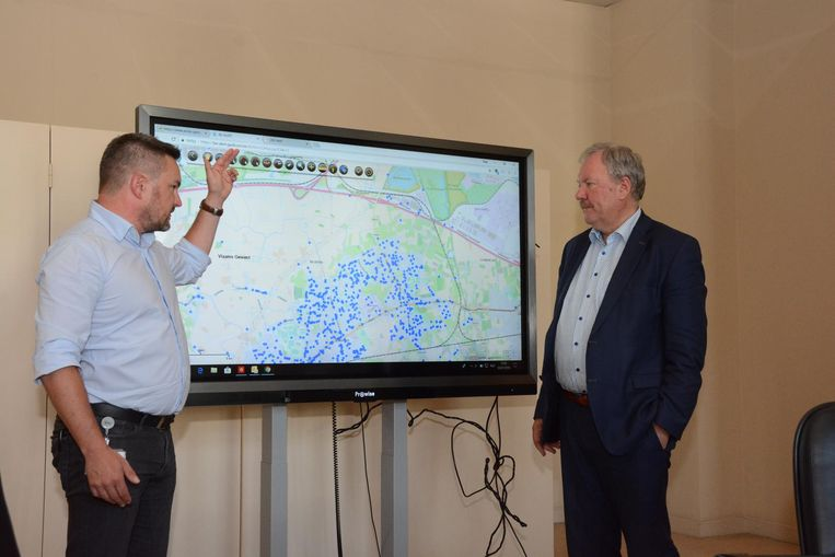 Yves D'Eer en Marc Van de Vijver kijken op de kaart hoeveel mensen het bericht ontvangen hebben.