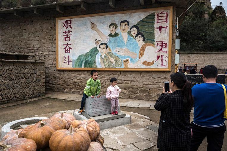 Ouders fotograferen hun kinderen voor een muurschildering die volgens de gids dateert uit de tijd dat Xi hier woonde. Beeld Foto Bryan Denton / The New York Times
