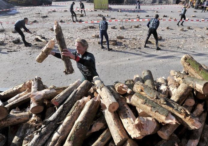 Surivalatlete dropt na afloop van het onderdeel houthakken de restanten van haar boomstam op de hoop tijdens de Needse survival. Foto Frans Nikkels