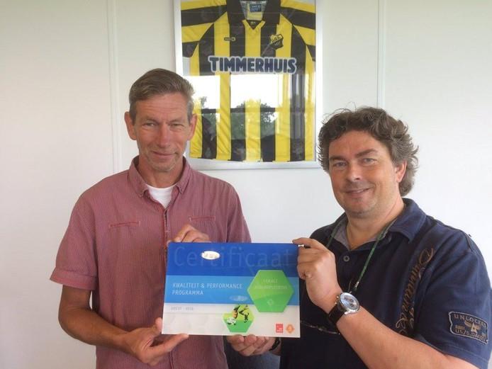 Jeugdvoorzitter Dinant Pas (rechts) van DOS'37 ontvangt de status lokale jeugdopleiding uit handen van KNVB-vertegenwoordiger Ab van der Velde.