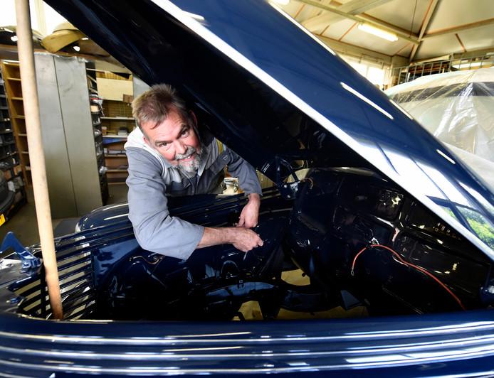 Gerrit de Koning klust aan de oude Opel Kapitän in z'n werkplaats.