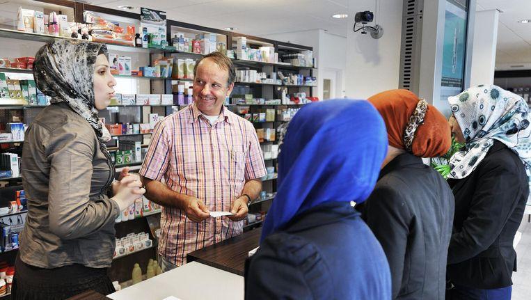 Paul Lebbink en zijn assistent helpen klanten in zijn apotheek in de Haagse Transvaalbuurt. Beeld Guus Dubbelman / de Volkskrant