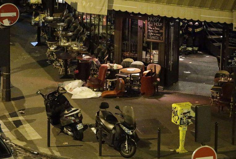 Een slachtoffer bedekt met een wit laken ligt op de grond bij het café La Bonne Biere. Beeld afp