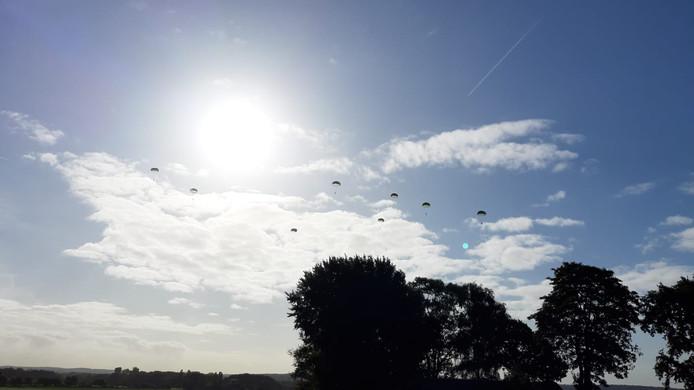 De eerste parachutisten sieren de zonnige lucht boven Groesbeek.