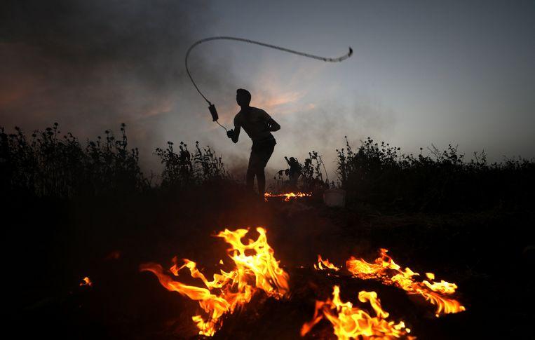 Een Palestijnse betoger gooit stenen naar Israëlische soldaten tijdens de bloedige demonstraties vorige week vrijdag in Gaza.  Beeld EPA