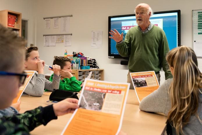 Cees van Roessel geeft uitleg over de bevrijding van zijn dorp aan de groepen acht van basisschool De Klim-Op in Haaren.