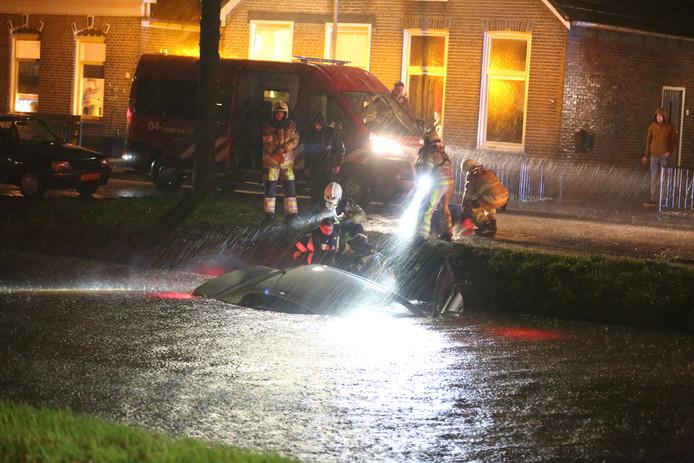Hulpdiensten bij de auto die in de Hoofdvaart belandde in Dedemsvaart.