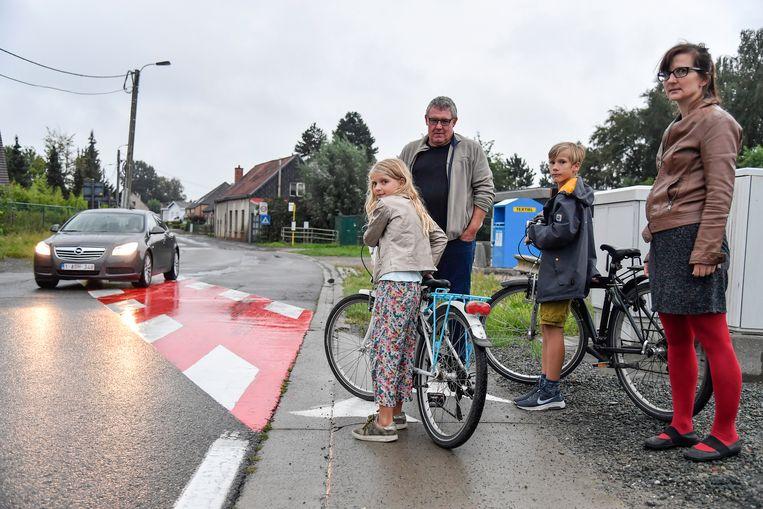 Tine Moens met haar kinderen aan de fietsoversteekplaats die aan een bocht ligt.