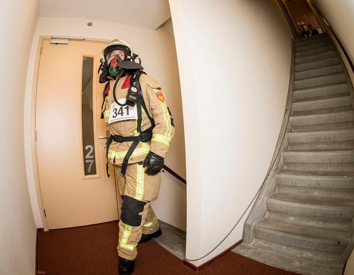 Enorm zwaar, maar ook heel stoer: brandweerman Nick Averdijk beklimt de toren in z'n werkkleding. Foto: Emiel Muijderman