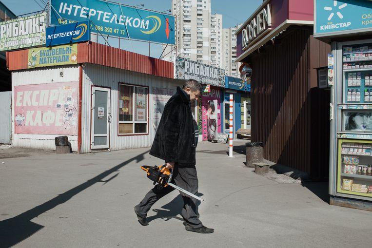 Een man probeert een Stihl-kettingzaag te verkopen bij een bushalte in Kiev. Beeld Emile Ducke