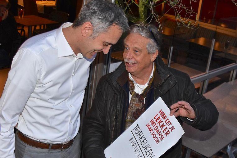 Jan, uitbater van restaurant Nata op de Grote Markt, ontvangt een affiche van de Unizo-voorzitter. RECHTS: de affiche.