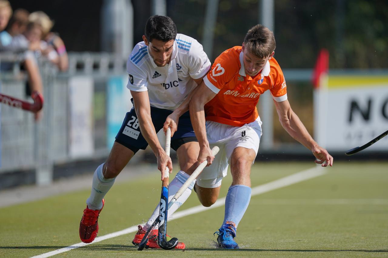 Federico Fernandez Onega van HC Tilburg in duel met Thierry Brinkman van HC Bloemendaal.