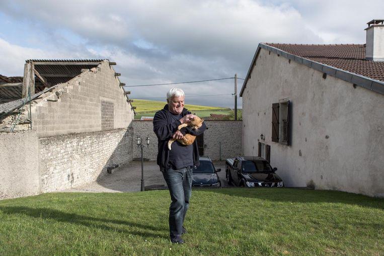 Michel Depp bij zijn huis in Vaux-la-Grande, met links de ingestorte woning van zijn buurman Beeld null