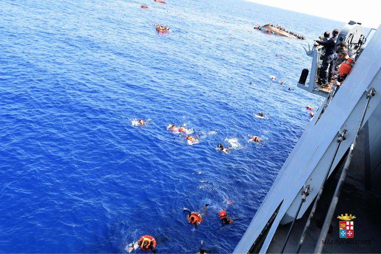 Migranten zwemmen naar een schip van de Italiaanse marine nadat hun boot is omgeslagen voor de Libische kust, 25 mei. Beeld afp