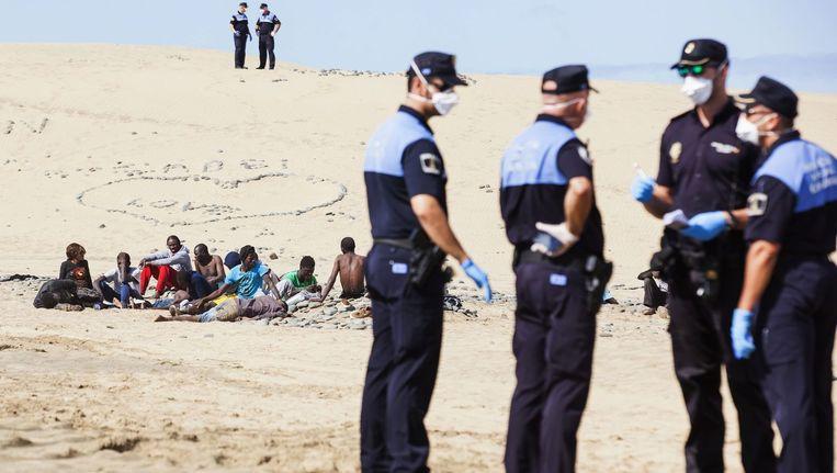 Een groepje immigranten wacht hun lot af op het strand van Maspalomas.
