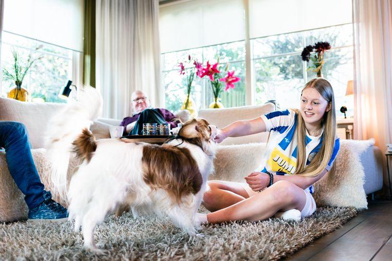Fleur Harshagen (18) thuis bij haar vader (links buiten beeld) in Lienden, met haar opa op de bank. Al vijftien jaar verplaatst Fleur zich tweemaal per week tussen de huizen van haar co-ouderende vader en moeder Beeld null