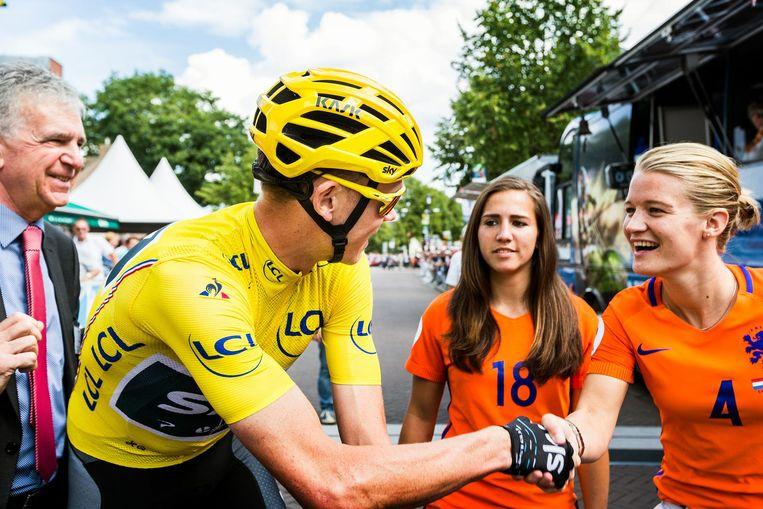 Voetballers Mandy van den Berg en Vanity Lewerissa van het Nederlands elftal begroeten de Tourwinnaar. Beeld Jiri Buller / de Volkskrant