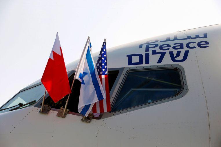 De vlaggen van landen die onderdeel uitmaken van het akkoord: Bahrein, Israël en de VS werden bevestigd aan het vliegtuig vlucht El Al 973 dat zondag naar de Bahreinse hoofdstad vliegt. Beeld AFP