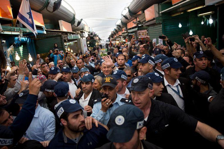 Premier Netanyahu bezoekt, omringd door beveiligers, een markt in Tel Aviv. Beeld AP