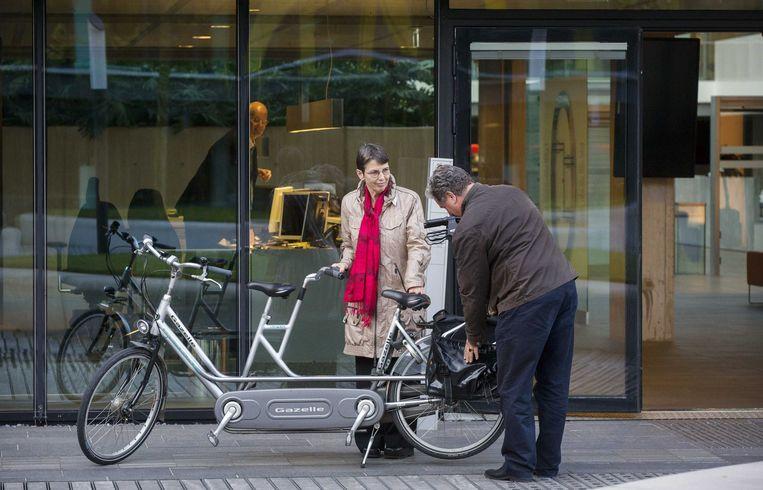 De staatssecretaris en haar chauffeur bij het ministerie van Financiën, op het punt een rit op de tandem af te leggen. Beeld anp
