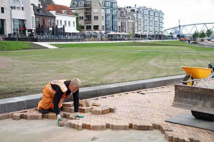Terwijl de eerste grassprieten de kop opsteken, zorgt een stratenmaker voor een nieuw plaveisel.