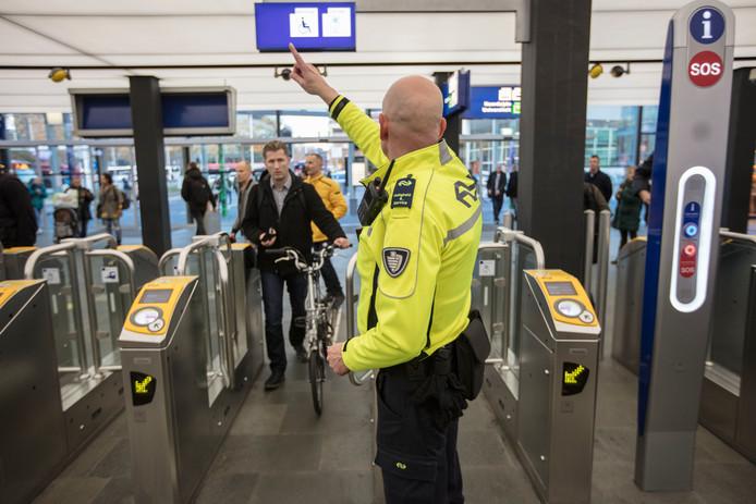 Medewerkers van de NS houden de toegangspoortjes in de gaten op het station in Eindhoven.