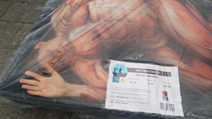 Twee activisten gaan 'verpakt' in een grote vleesschaal op het Achterom liggen.