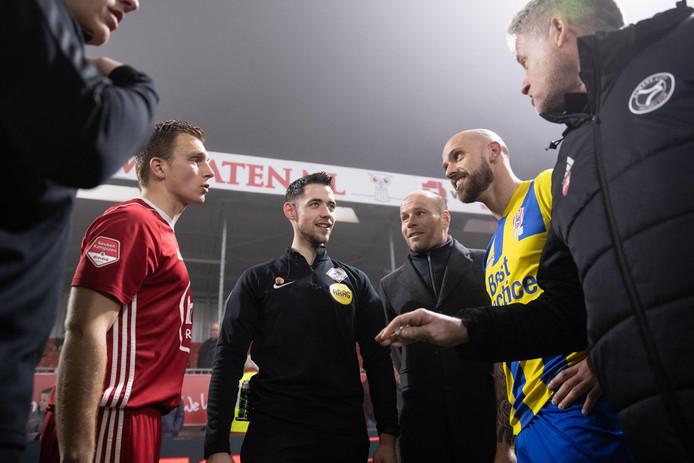 Scheidsrechter Nagtegaal overlegt met de aanvoerders van beide teams wat te doen.