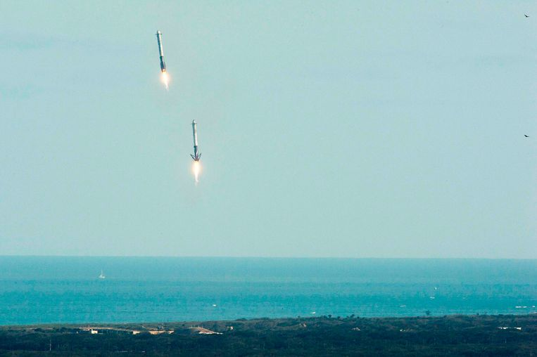 De boosterraketten van de Falcon Heavy keren terug op Kennedy Space Center, waar ze keurig landen. Beeld afp
