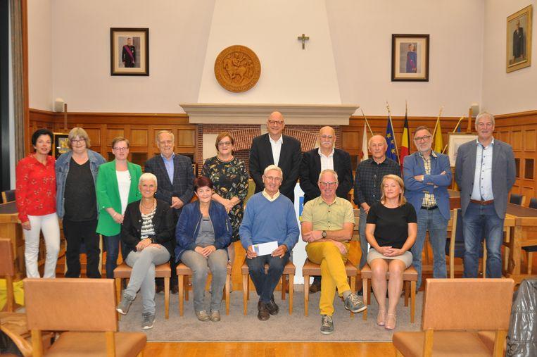 De prijsuitreiking van vorig jaar, traditioneel in de raadzaal van Tessenderlo. Het zijn de tien winnaars en de organisatoren van de drie zoektochten.