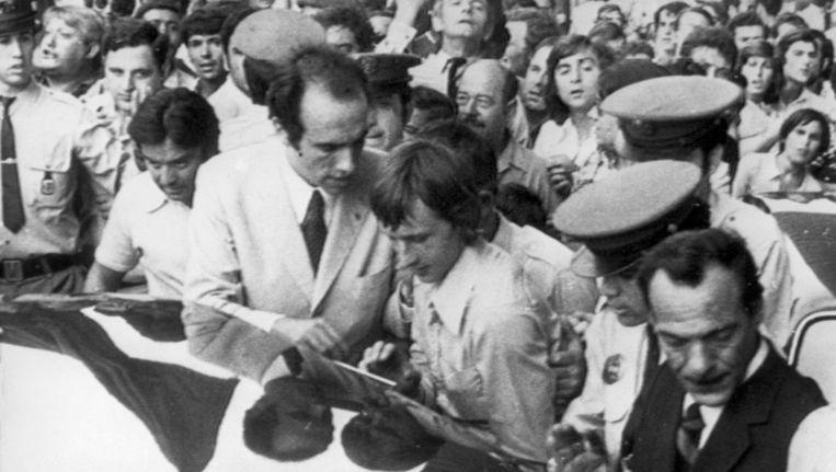 Aankomst van Johan en Danny Cruijff op het vliegveld van Barcelona, omringd door agenten en gadegeslagen door een menigte. Beeld anp