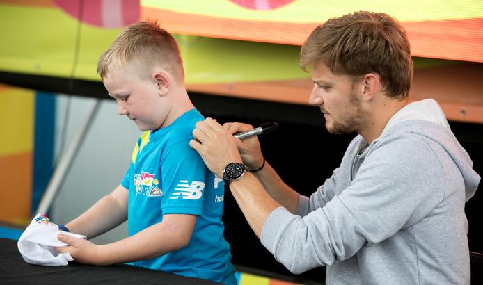 De Belgische tennisser David Goffin geeft een handtekening aan een jonge fan.