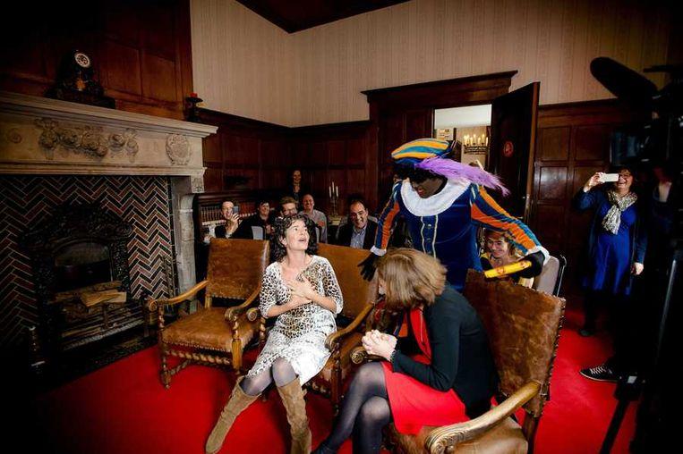 Presentatrice Dieuwertje Blok van het Sinterklaasjournaal wordt verrast door een Zwarte Piet. Beeld anp
