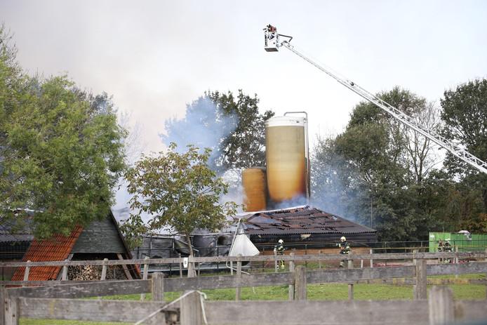 De brandweer bestrijdt het vuur in de stal met een hoogwerker.