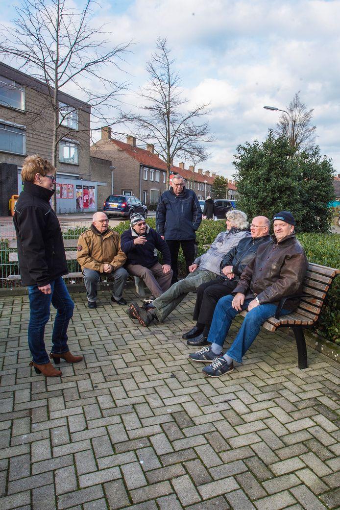 Ilonka Mudde (l) van Buurt Bestuurt geeft de 'kletsers' uitleg de overkapping die hun dagelijkse samenzijn comfortabeler maakt.