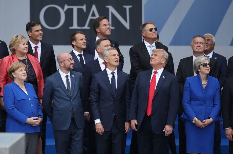 Op de eerste rij kijken Angela Merkel, Charles Michel, Jens Stoltenberg en Theresa May naar links, terwijl Donald Trump rechts iets heeft gezien.