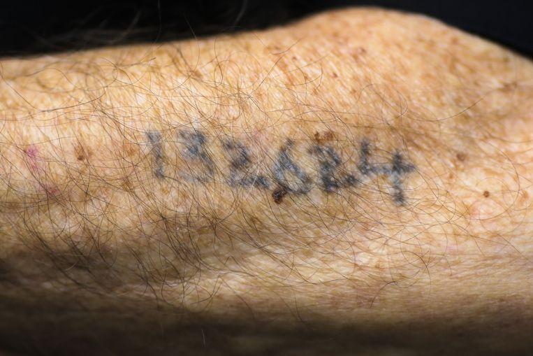 Auschwitz-overlevende Leon Schwarzbaum toont zijn nummer, vlak voor de uitspraak tegen Gröning. Schwarzbaum was speciaal naar de rechtbank gekomen om te horen hoeveel straf Gröning zou krijgen. Beeld null