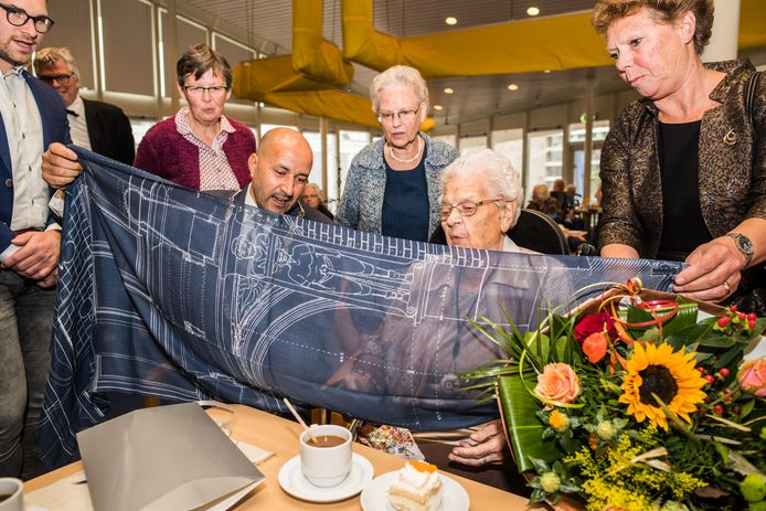 Burgemeester Marcouch van Arnhem  vouwt de sjaal uit die hij net cadeau heeft gedaan aan de 109 jaar geworden Cornelia Boonstra-van der Bijl in verzorgingshuis Vreedenhoff.