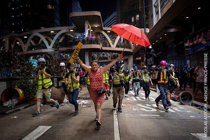 Foto van de Deense fotograaf Nicolas Asfouri, genomineerd in de categorie World Press Photo Story of the Year . Een vrouw houdt als protest een paraplu omhoog in het Causeway Bay district van Hongkong op 1 oktober 2019.