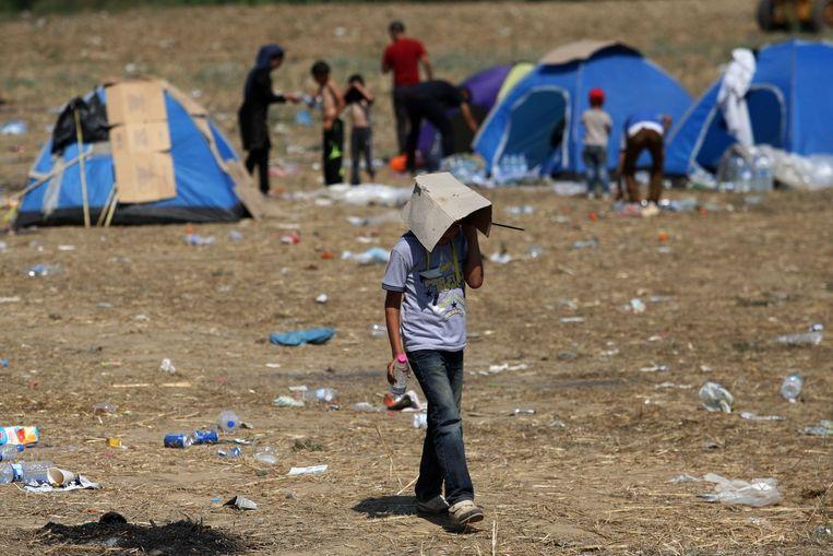 Een kind aan de grens tussen Griekenland en Macedonië loopt met een stuk karton op zijn hoofd om zich tegen de zon te beschermen. Beeld afp
