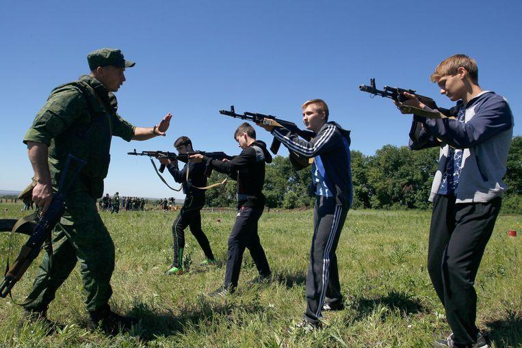 Een instructeur leert schoolkinderen hoe ze een wapen moeten gebruiken in de buurt van Donetsk. Beeld EPA