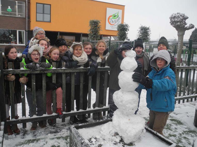 De leerlingen van basisschool De Kiem voltooien de eerste - kleine - sneeuwman van het jaar.