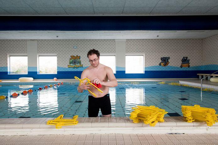 Een medewerker van het Tielse zwembad maakt van de sluiting gebruik om de kledinghangers eens goed schoon te maken.