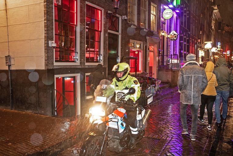 Een motoragent op de Amsterdamse Wallen, een topattractie van Amsterdam. Beeld Guus Dubbelman / de Volkskrant
