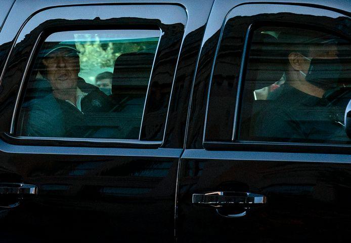 Donald Trump kijkt vanuit de wagen op weg naar het Witte Huis.