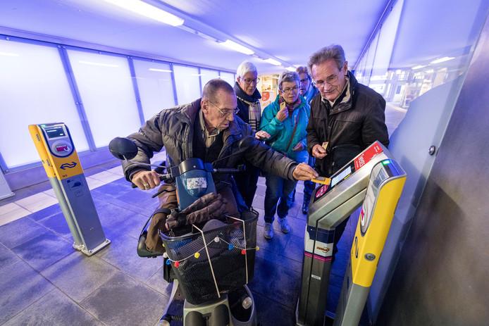 Ouderen checken in bij het Centraal Station van Hengelo voor de proeftocht. Grietje Koopman (linksachter) kijkt samen met Bert Nouwen (rechts) mee of het goed gaat.
