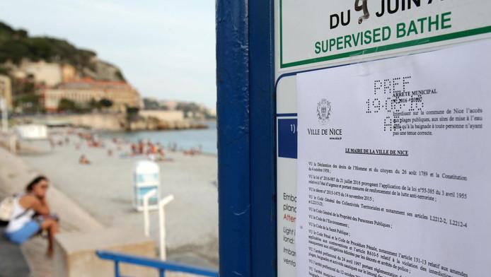 Op een bord staan de nieuwe kledingvoorschriften die gelden op het strand van Nice.