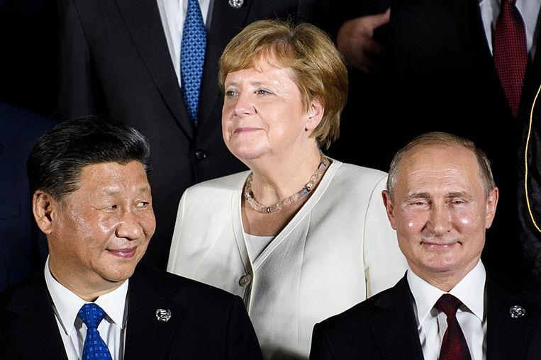Poetin poseert met Xi Jinping van China en de Duitse Bondskanselier Angela Merkel, die hij een 'kardinale fout' toedicht in het binnenlaten van asielzoekers uit Syrië in 2015. Beeld AFP