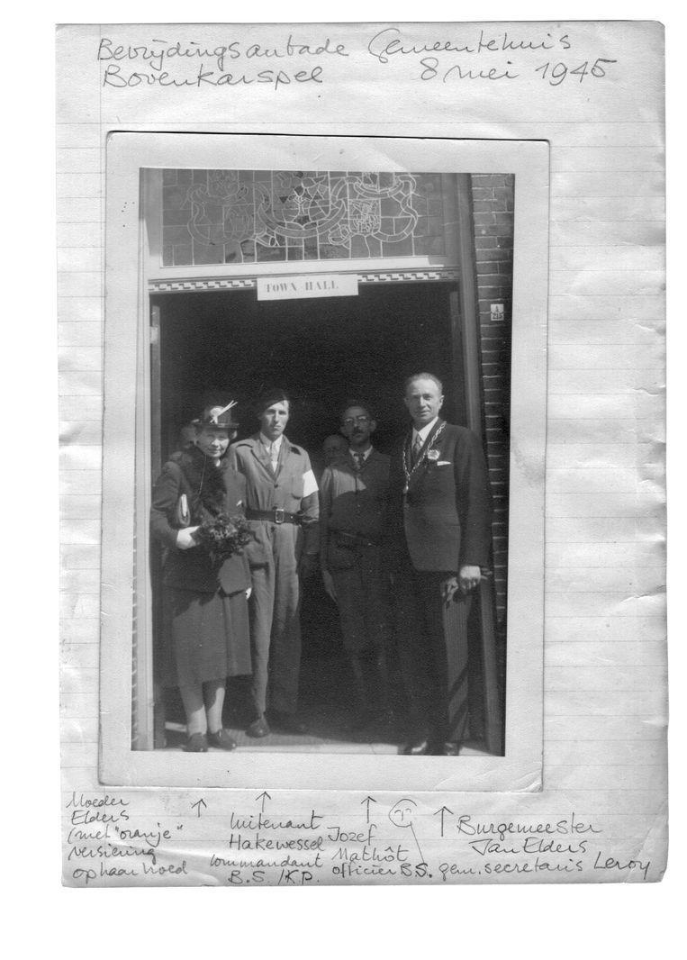 De burgemeester (rechts) en zijn vrouw Jo in de deuropening van het gemeentehuis, samen met leden van het verzet. Beeld RV